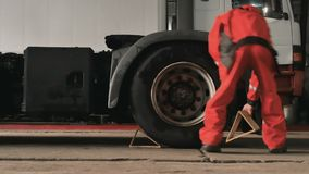 Worker puts wooden under-wheel supports for truck. To protect it from suddenly motion. Car service station. Man preparing lorry for repairing stock video