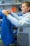 Worker putting on blue coat before starting to work stock photo