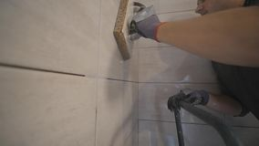 Worker putting fugue on the wall in the kitchen. Tile grouting stock video
