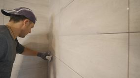 Worker putting fugue on the wall in the kitchen. Tile grouting stock footage