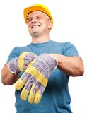Worker putting on leather protection gloves. Blue collar worker with yellow helmet putting on leather protection gloves Royalty Free Stock Image
