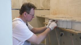 Worker is putting the piece of tile. stock footage