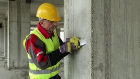 Worker with putty knife at construction site. Worker in yellow hard hat with putty knife at project site stock video