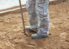 Worker with rake while crushing the ground Stock Photography