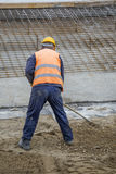 Worker with rake working. On ground leveling at construction site Royalty Free Stock Images