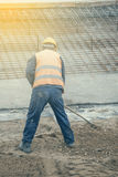 Worker with rake working. On ground leveling at construction site. Vintage style Stock Image