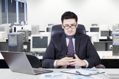Worker reading a message in office room Royalty Free Stock Photos