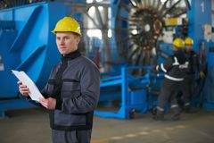 Worker reading paper documents while standing at factory. Young Worker reading paper documents while standing at factory with working machines on background stock images