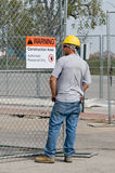 Worker Reading Warning Sign Stock Image