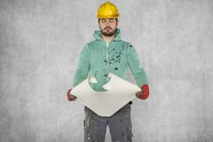 The worker reads the construction plans with great interest. Protective helmet on the head Stock Photography