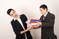 Worker receiving many files from his happy boss. Royalty Free Stock Image