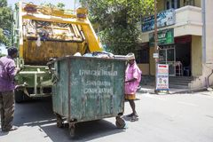 Worker of recycling garbage collector truck loading waste and trash bin. PONDICHERY, PUDUCHERRY, TAMIL NADU, INDIA - March circa, 2018. Unidentified workers of royalty free stock photography