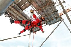 Work at height by rope access. Worker with red boiler suit work at height low down by rope access stock image