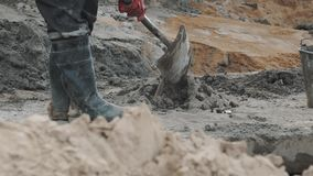 Worker in red gloves gathering cement in pile using shovel at building site stock footage