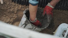 Worker in red rubber gloves take cement from bucket and put it on ribbed pipe stock footage