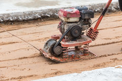 Worker with red soil compactors in construction site royalty free stock photos