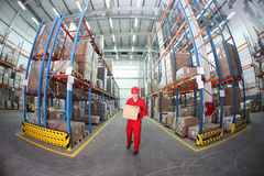 Worker in red uniform with box in warehouse