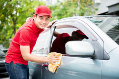 Worker in red uniform cleaning car. Auto detailing and valeting, service concepts stock photos