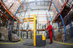 Worker in red uniform at work in warehouse stock photo