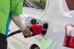 Worker refilling the car with fuel. Royalty Free Stock Image