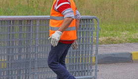 Worker with reflective jacket moves iron hurdles Stock Photo