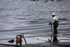 Worker remove crude oil from a beach Stock Photos