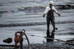 Worker remove crude oil from a beach Royalty Free Stock Photo