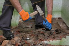 Home renovation, bathroom demolish. Worker remove, demolish old bathtub and tiles with hammer and chisel in a bathroom royalty free stock images