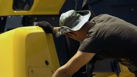 Worker remove hooks from detail of a tractor after carrying it. Worker remove hooks from truck body. Delivery of cargo for machine-building production stock footage