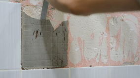 The worker removes the old ceramic tile from the wall in the bathroom stock video footage