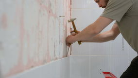 The worker removes the old ceramic tile from the wall in the bathroom stock video