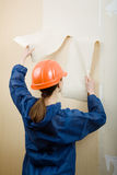 Worker removes old wallpaper Stock Photo