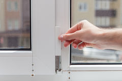 The worker removes the protective plug from the element of the plastic window. Preparing a plastic window for minor repairs Royalty Free Stock Image