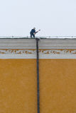 Worker removes snow from the roof of the Arsenal building Royalty Free Stock Images