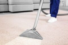 Worker removing dirt from carpet, closeup. Cleaning service