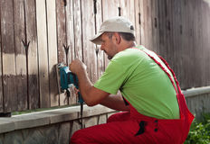 Worker removing old paint from fence royalty free stock photography