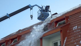 Worker removing snow on the roof of the building stock video