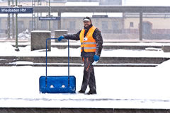 Worker removing snow from the station platform Stock Images