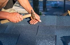 Worker repair corner bitumen roof shingles with hammer and nails stock image