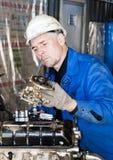 Worker repair the motor. Industrial area. Worker repair the motor Stock Photography