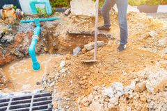 Worker repair pipe plumbing water main broken. Use shovel to dig a hole underground on the road.  Stock Images