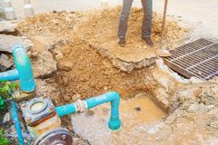 Worker repair pipe plumbing water main broken. Use shovel to dig a hole underground on the road.  royalty free stock photos