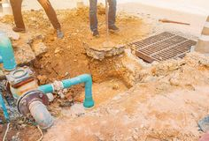 Worker repair pipe plumbing water main broken. Use shovel to dig a hole underground on the road.  stock image