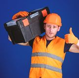 Worker, repairer, repairman, builder on confident face carries toolbox on shoulder. Man in helmet, hard hat holds. Toolbox and shows thumb up gesture, blue stock photos