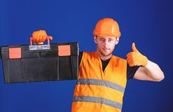 Worker, repairer, repairman, builder on confident face carries toolbox on shoulder. Repair consultation concept. Man in. Helmet, hard hat holds toolbox and royalty free stock image