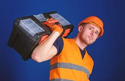 Worker, repairer, repairman, strong builder on thoughtful face carries toolbox on shoulder, ready to work. Repair and. Renovation concept. Man in helmet, hard royalty free stock images