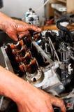 Worker repairing broken engine. Hands of a worker repairing broken engine Royalty Free Stock Photo