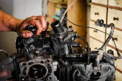 Worker repairing broken motor. In garage Stock Photography