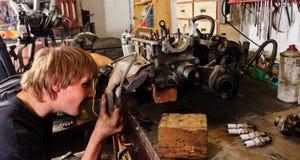 Worker Repairing car motor. Worker in garage with engine Royalty Free Stock Photo