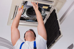 The worker repairing ceiling air conditioning unit. Worker repairing ceiling air conditioning unit Stock Image